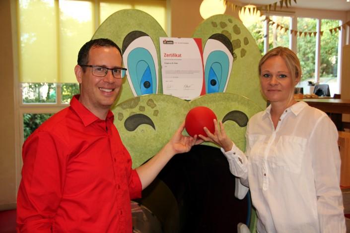 Das Foto zeigt Andreas Feldmann und Jennifer Leuthold, Krippenleitung und iPunkt-Beauftragte, mit dem iPunkt Zertifikat